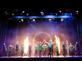 Cast standing on stage dressed in green costumes with flames lighting up the stage in front