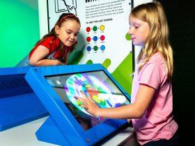 A girl mixes virtual colours on an electronic touch screen in the an exhibit kiosk