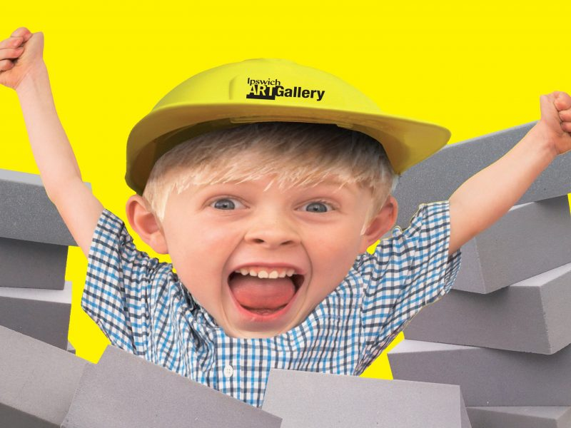 Excited young boy wearing a hard hat and bursting through grey foam bricks on yellow background.