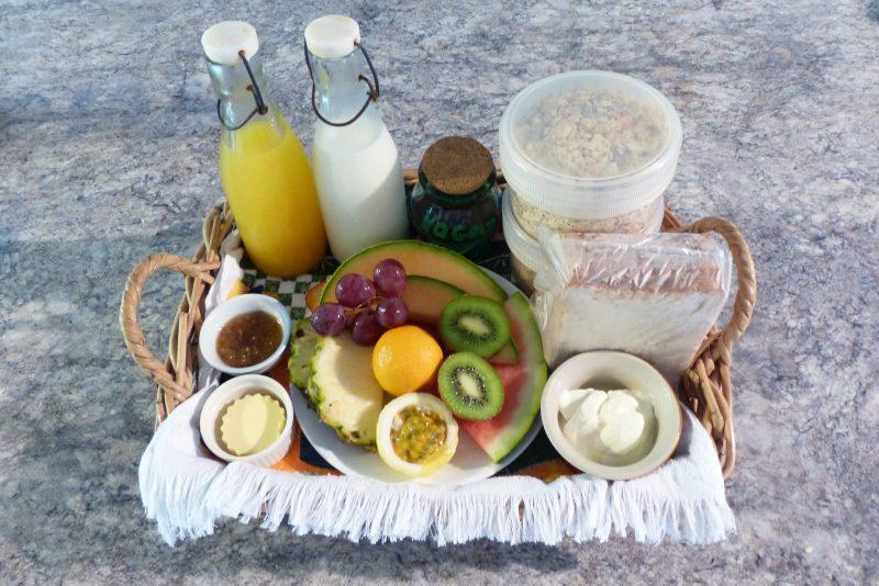 Basket containing fruits, cereals, jam, yoghurt, milk, juice and bread