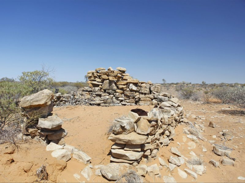 Ruins of rock walls on sandy dune.