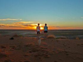 Children watching sunset on sandune.