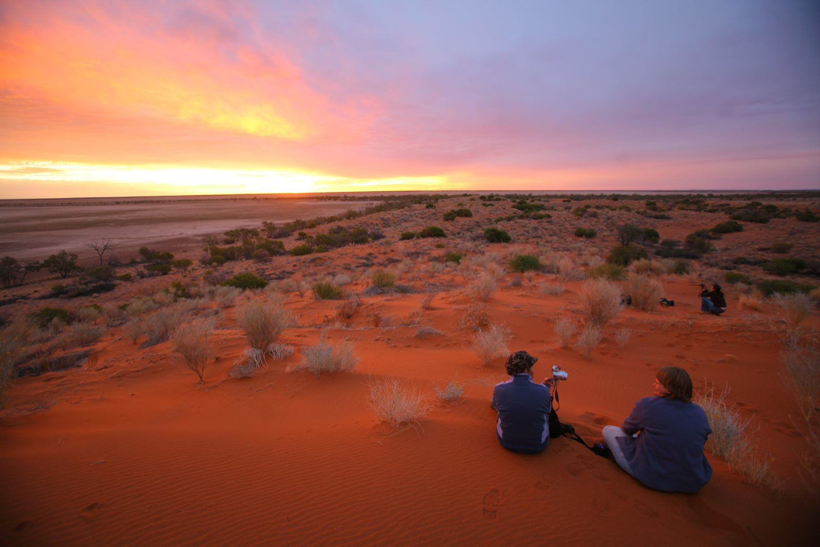 Visitors enjoying Diamantina's red sand hills and sunset.