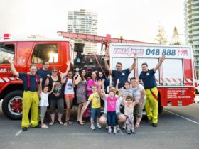 Families posing for photos beside the Fire Trucks with their Fire Fighters