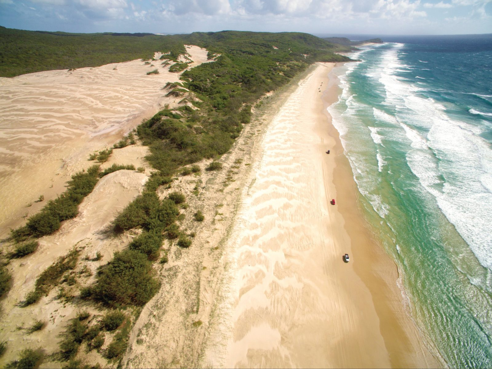 Long white sandy beach and vehicles, Fraser Island