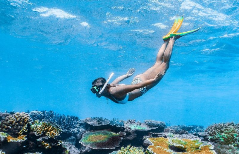 Woman snorkelling over coral