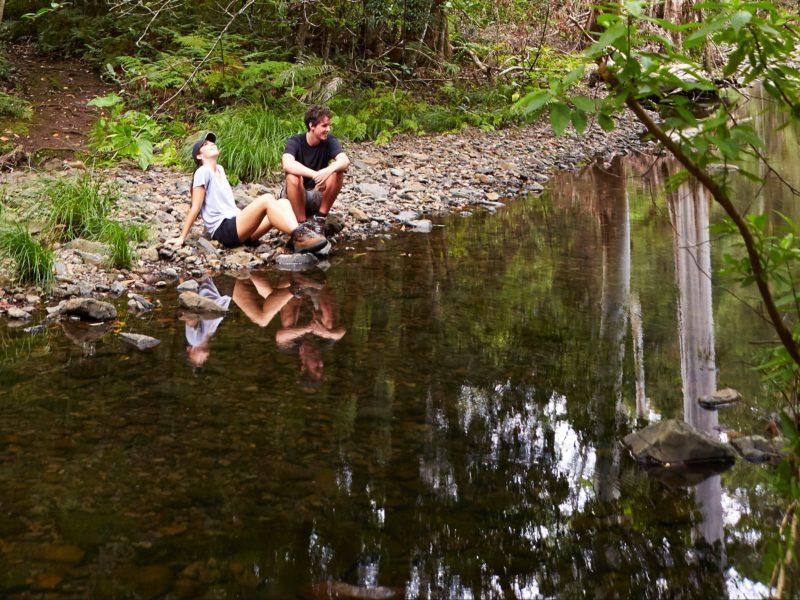Couple sitting on rocks beside creek.