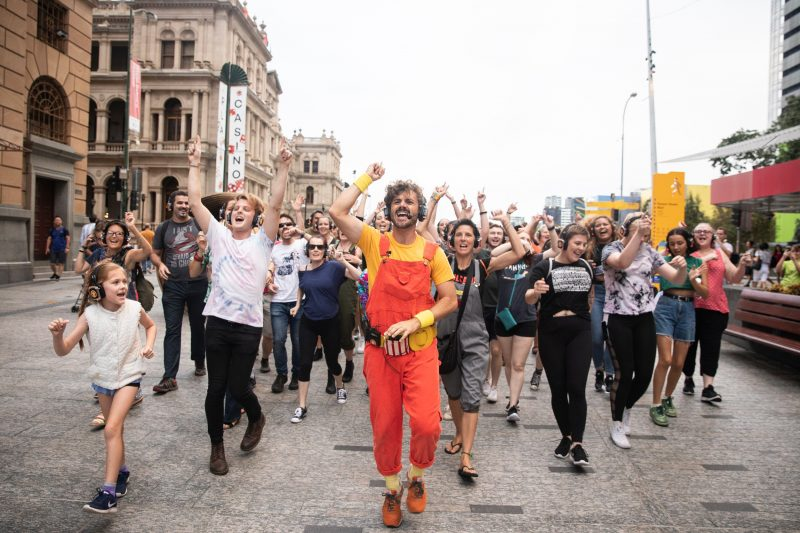 Dani Disco leads a group of 60 singing people through Queen St Mall in Brisbane.