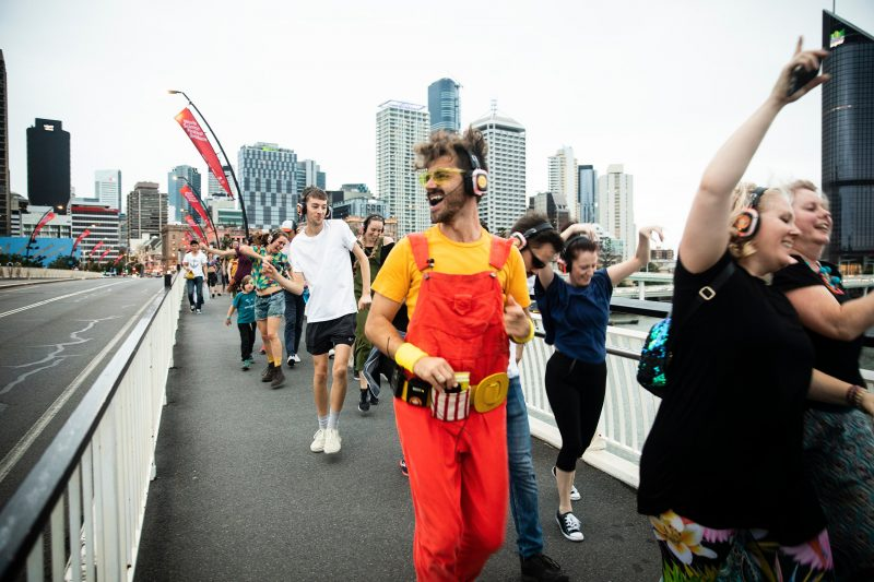Dani Disco leads a group of 60 dancing people over the Brisbane River