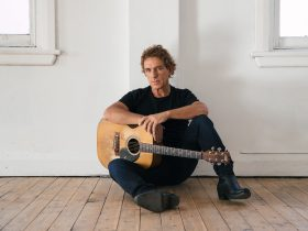 Ian Moss sitting against a white wall wearing black clothes, holding his acoustic guitar