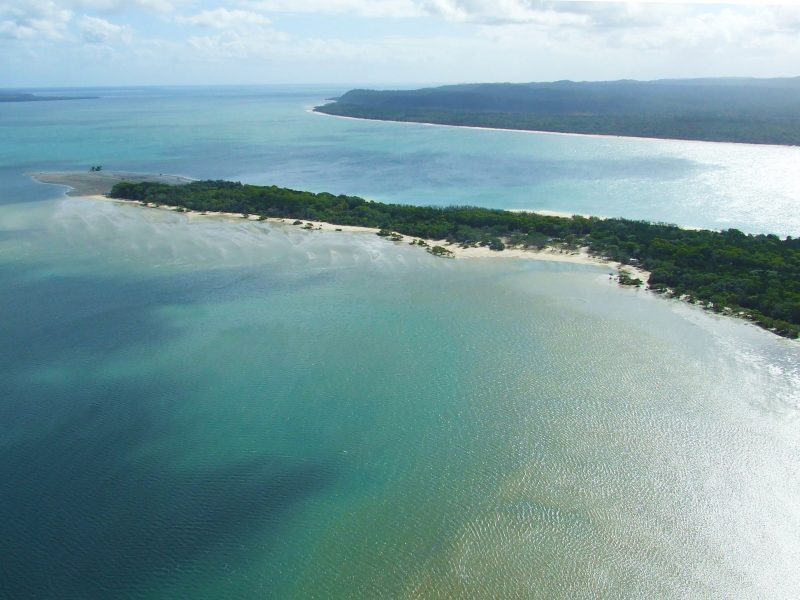Aerial shot of the narrow tree-clad peninsula surrounded by sandy bays and turquoise waters.