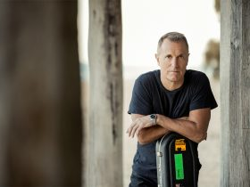 James reyne leaning on his guitar case