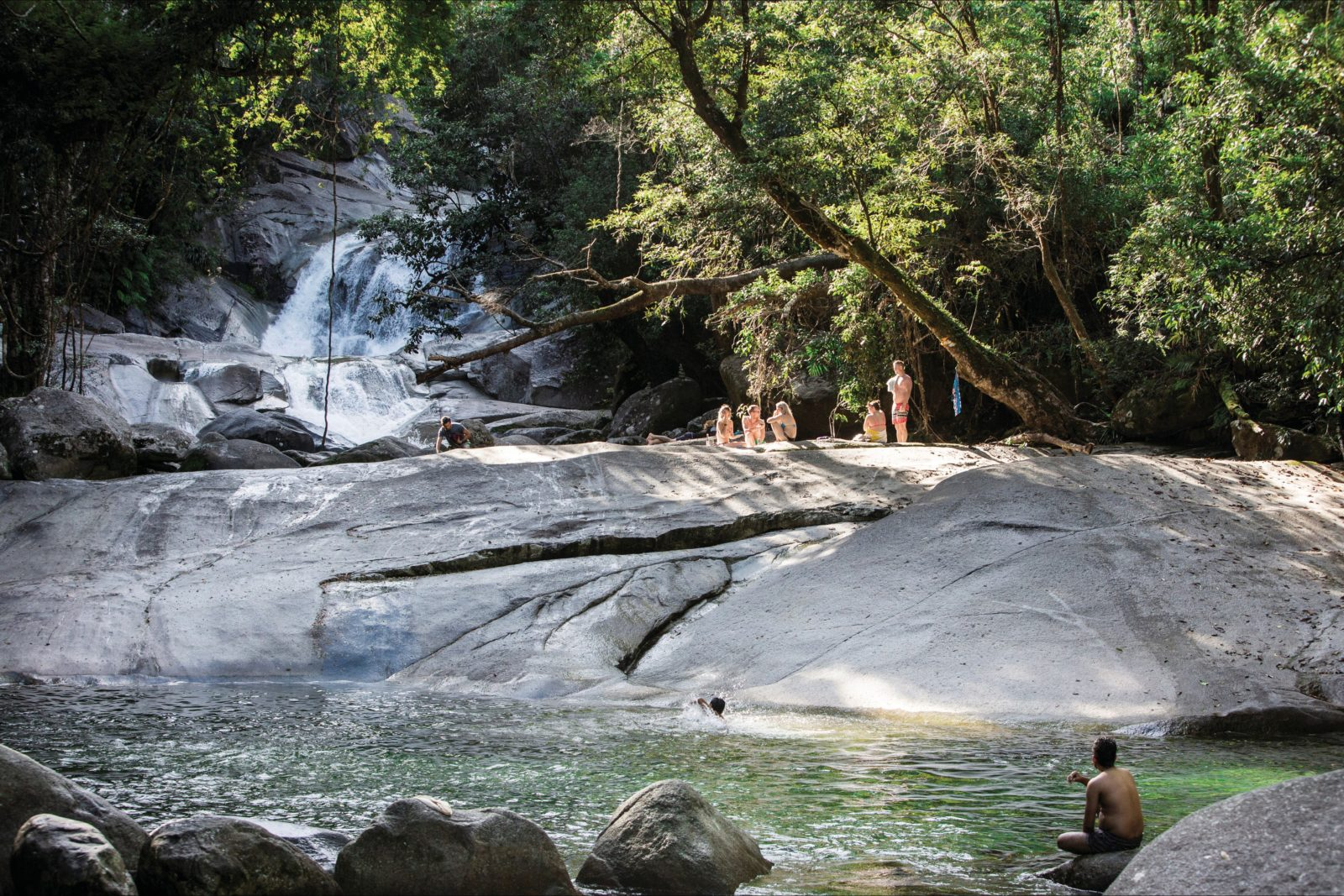 People on rock above bottom pool with waterfall in background.