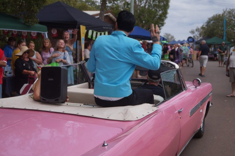 """Elvis"" arriving in the back of a pink Chevy through the crowds to the stage area."