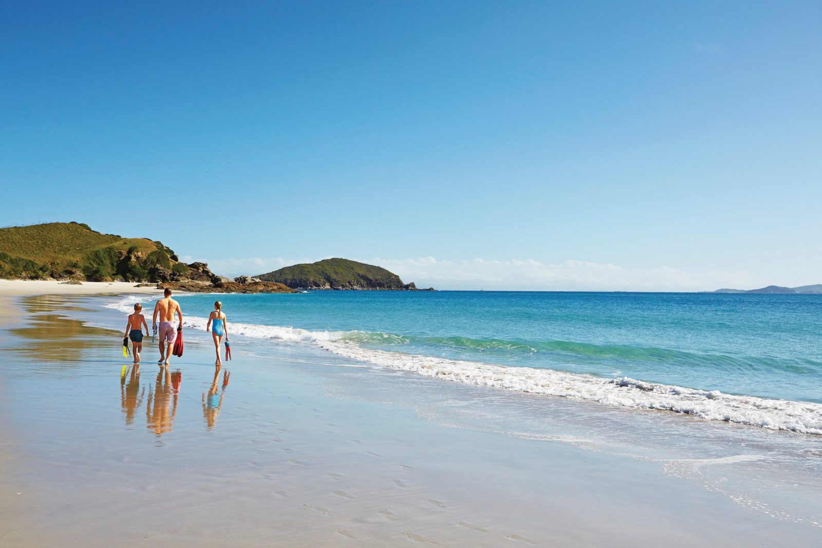 Family walking alonb beach near the shoreline, Keppel Islands