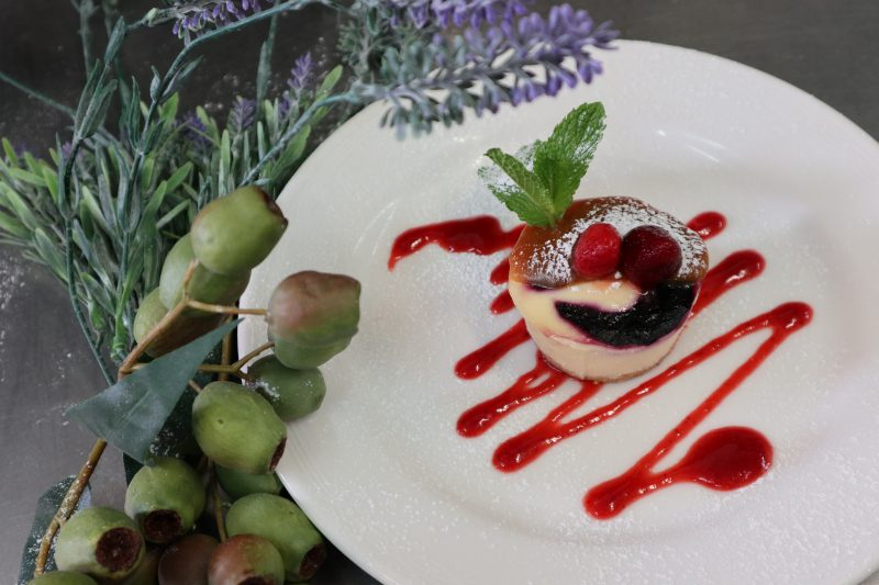 American style baked cheesecake on a swirl of berry coulis topped with fresh strawberries and mint
