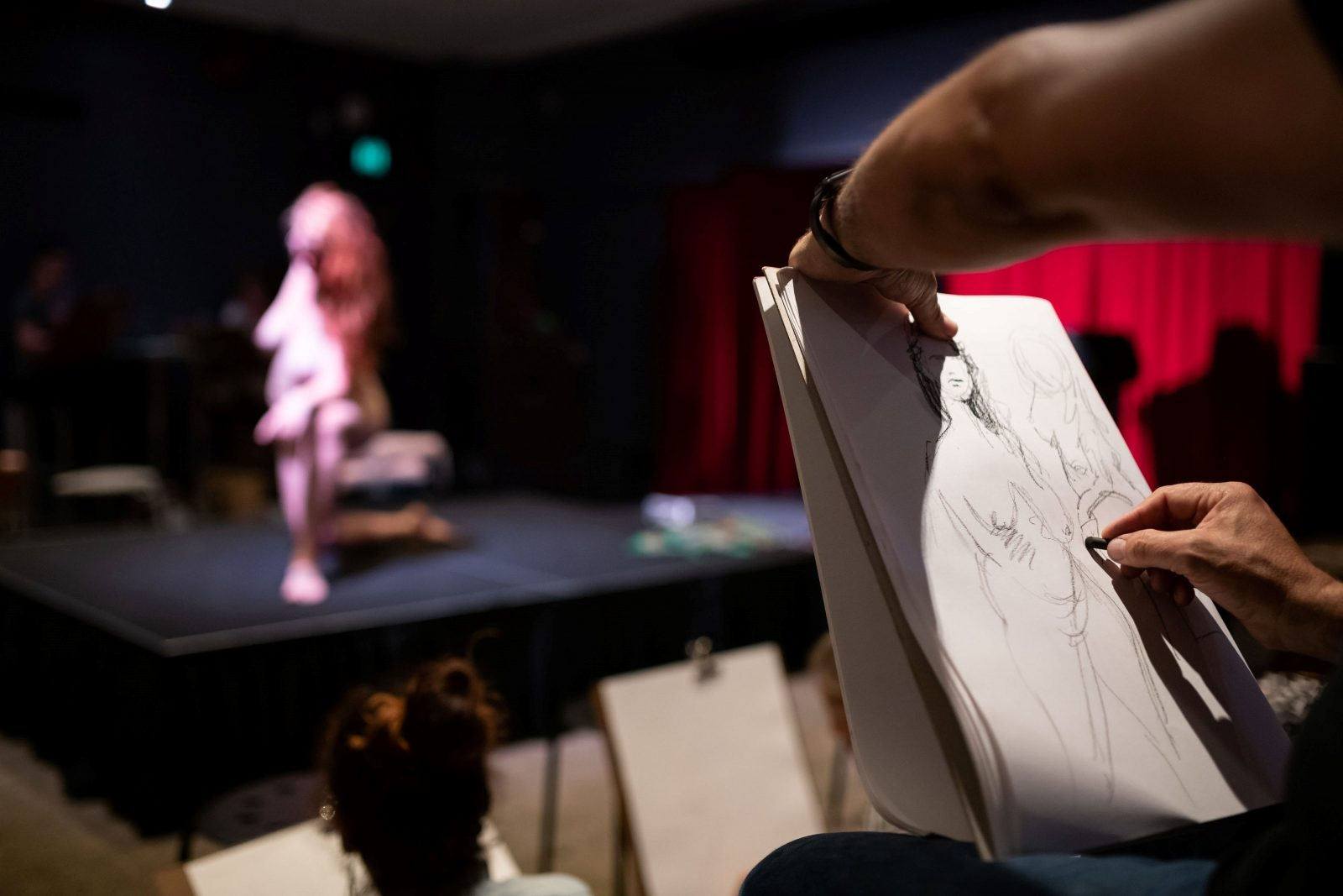 woman posing on a stage while people draw her on easels