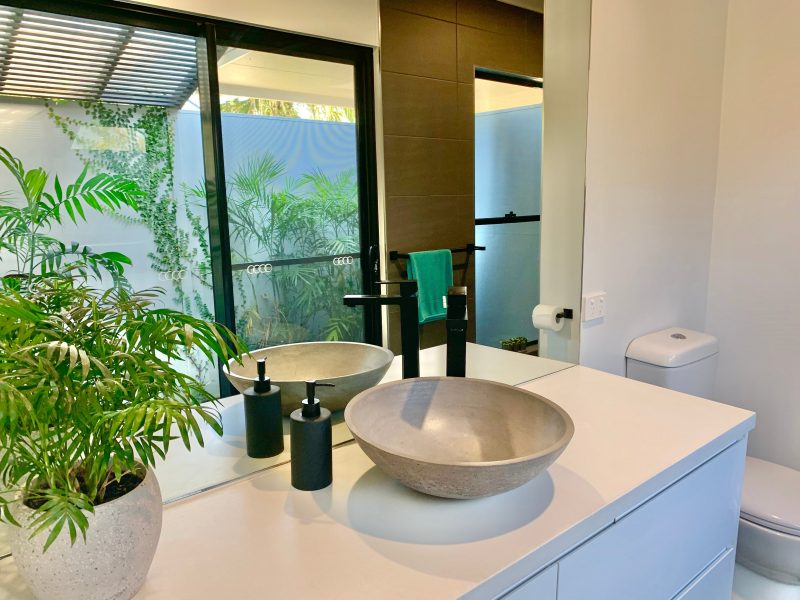 Ensuite showing basin and vanity with garden reflected in mirror