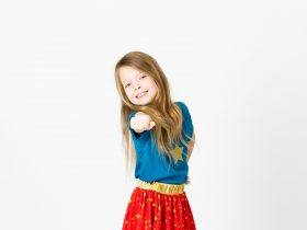 girl in blue shirt and red skirt pointing at the camera