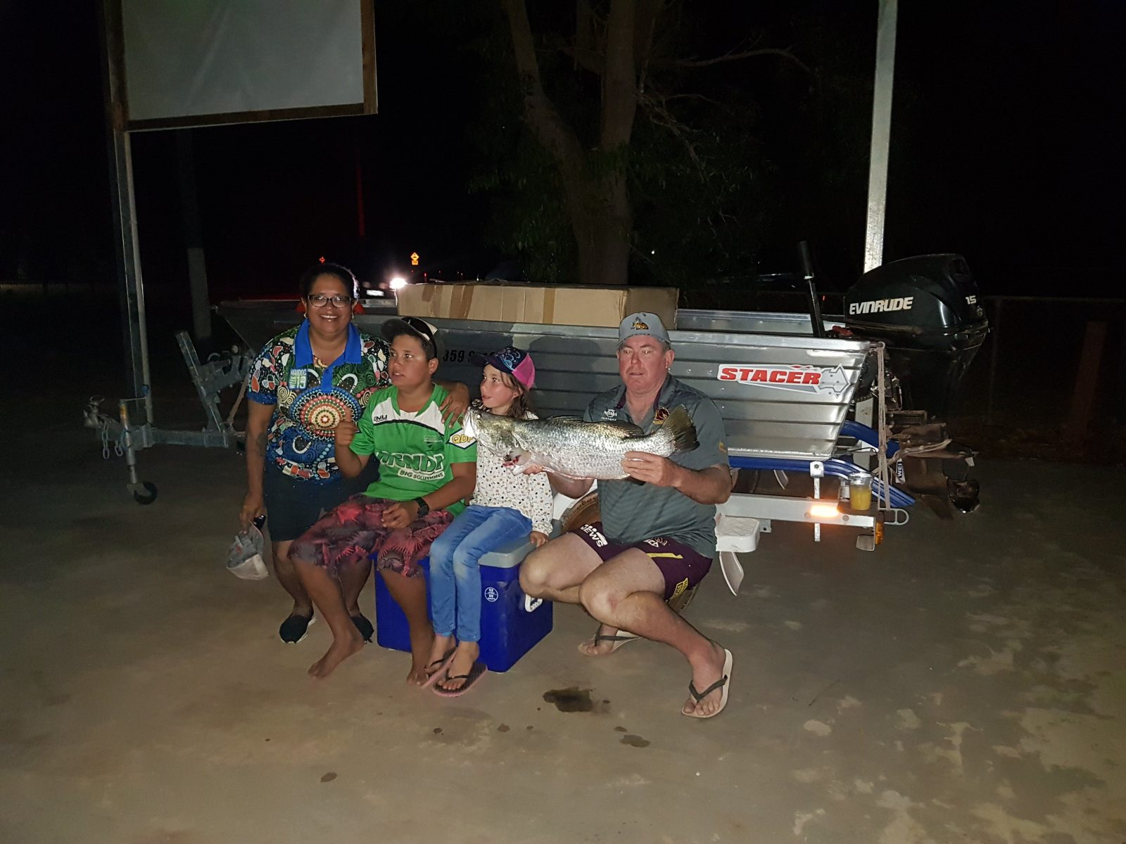 Winning family showing parents and two children with barramundi after weigh-in in the evening