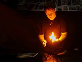 A magician stands holding a deck of cards. The cards have been set on fire.