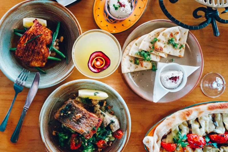 Birdseye view of a table of food, including Tenderised Calamari, Barramundi, and Haloumi Pizza