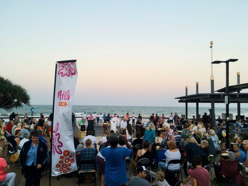Bargara beach at twlight. Crowds gathered at beachside for drumming circle and activities.