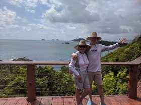 A caucasian man and woman stand on a wooden deck with tropical islands and the sea in the background