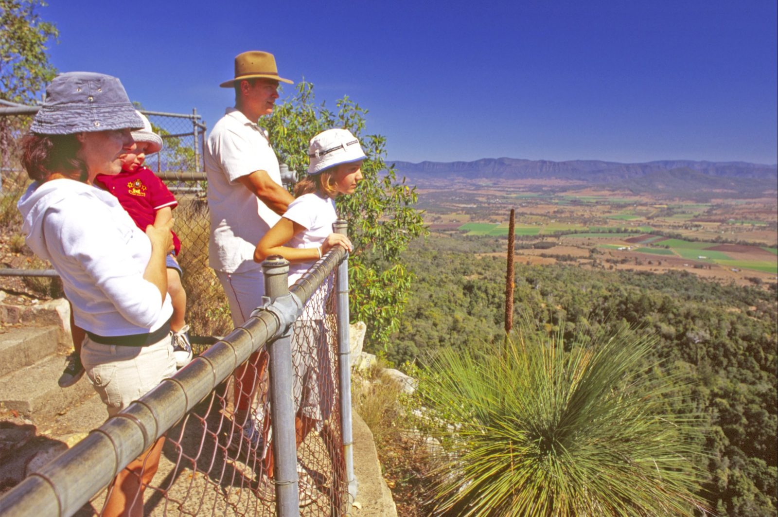 Young family at high lookout with views over bushland, farmland and mountains.