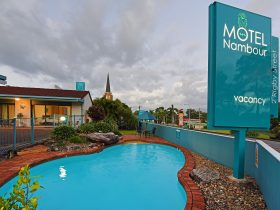 The pool and big sign of Motel In Nambour