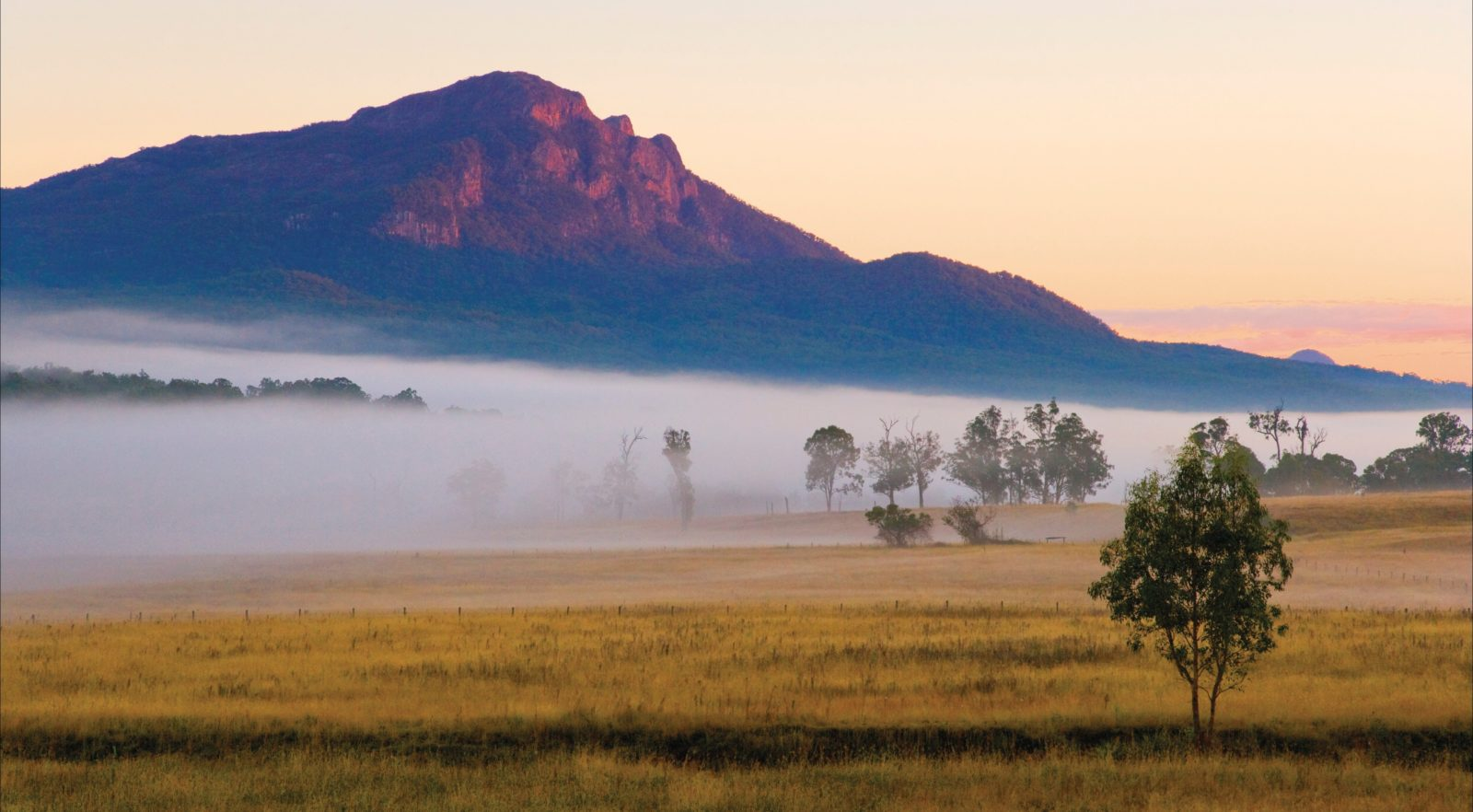 Mount Maroon with base shrouded in fog and farmlands in foreground.