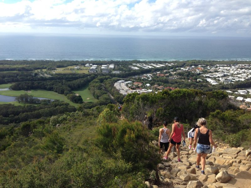 A group of walkers pick their way through rocky track down a hill slope with coastal plain below.