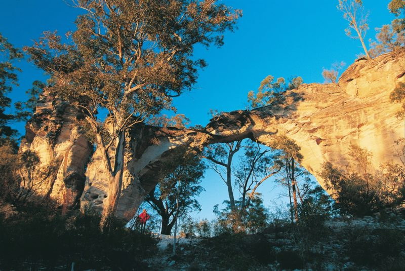 Person standing under Marlong Arch rock formation.
