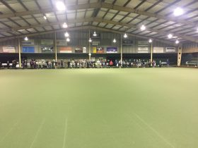 Players enjoying barefoot bowls under cover at night