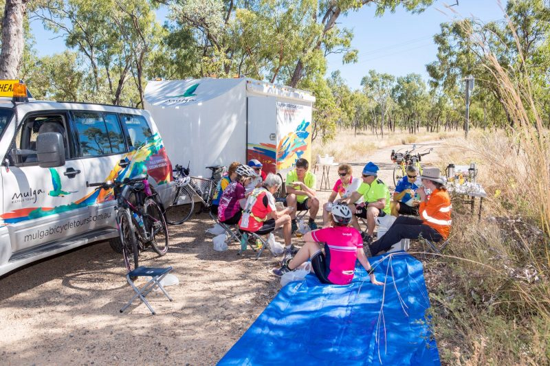 Guests sitting on stools next to Mulga Bicycle Tours trailer