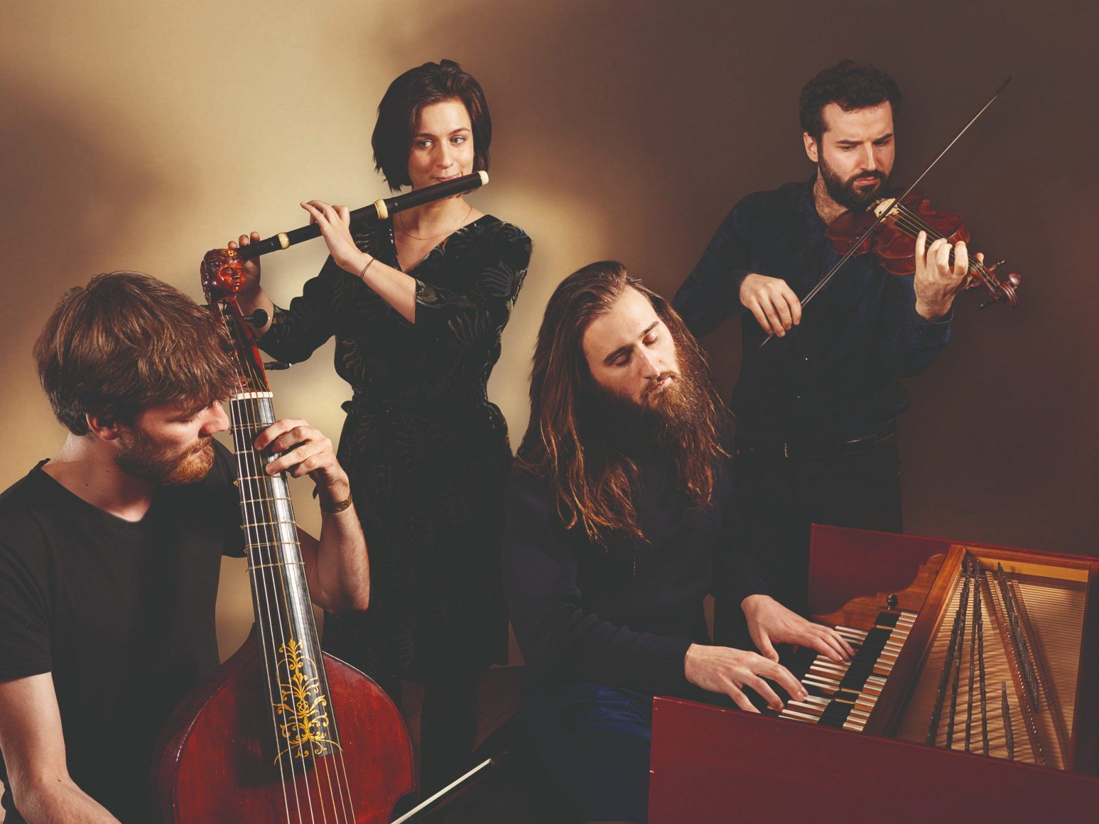 Four musicians play instruments from the renaissance and baroque era. Harpsichord, flute and strings