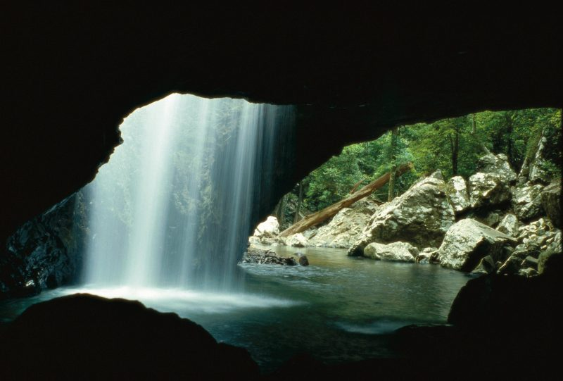 A sheet of white water, backlit by sunlight, falls into a dark rockpool, underneath a rock arch.