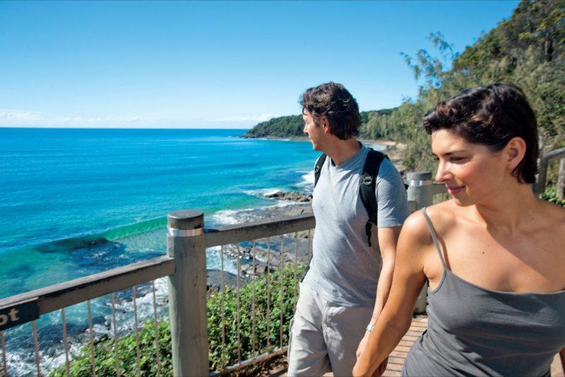 Couple walking along boardwalk on coast.