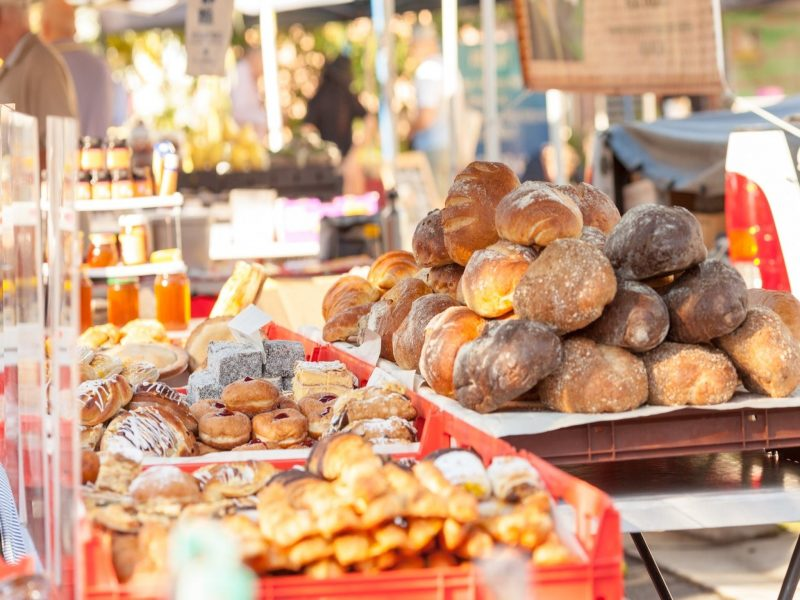 Fresh breads and pastries on display at a market stall.