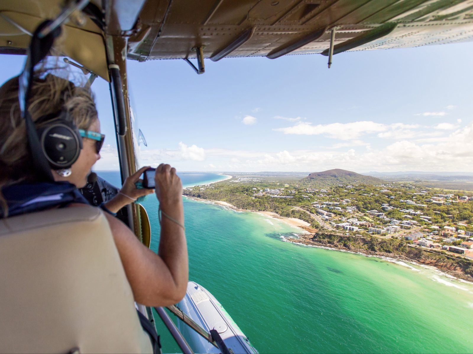 Seaplane passenger takes photos over Mt Coolum with doors off