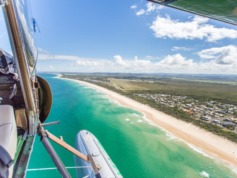 Seaplane over Marcoola, Sunshine Coast with doors off
