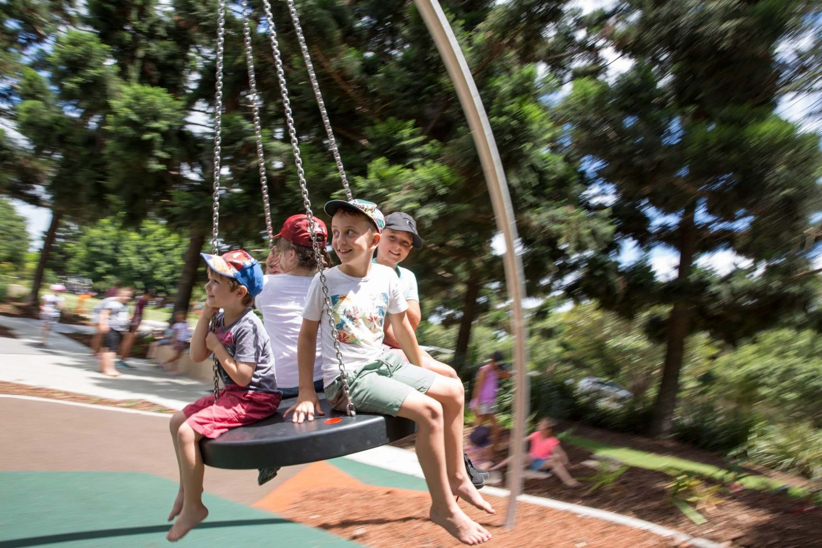 Four kids sitting on a large round swing at Pine Rivers Park