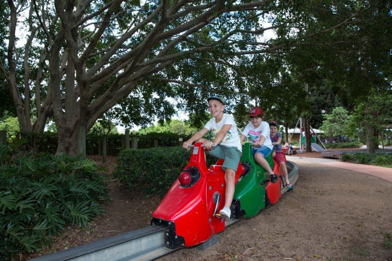 Two young boys on a pedal powered train in park