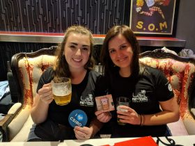 Two Pint of Science volunteers showing the coasters from the previous year's event.