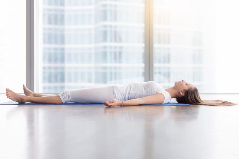 Young woman lying on yoga mat meditating