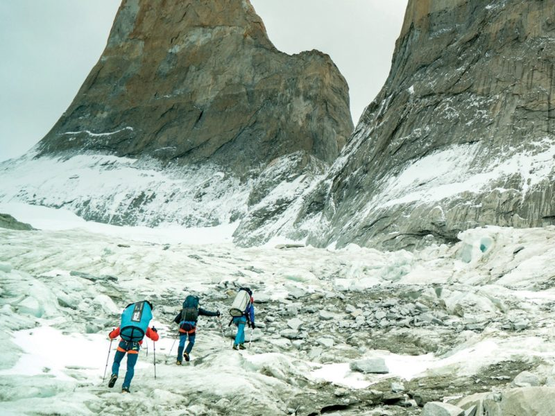 3 people climbing a snowy mountain