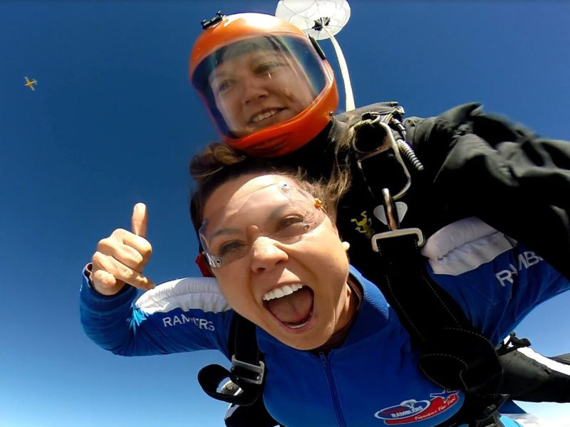 Anna thumbs up in freefall with Tandem Master Sara