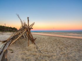 Large triangular tent made out of sticks and branches on the beach at sunset