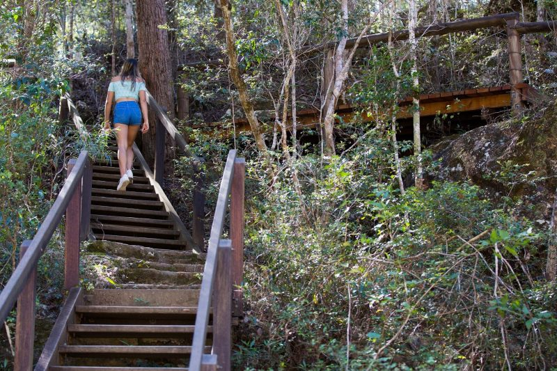 Woman walking up stairs towards Rocky Hole