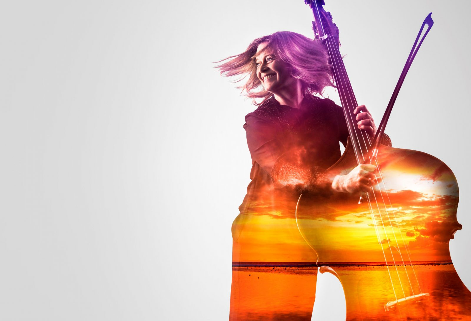 Bass player with superimposed sunset looking into distance joyfully